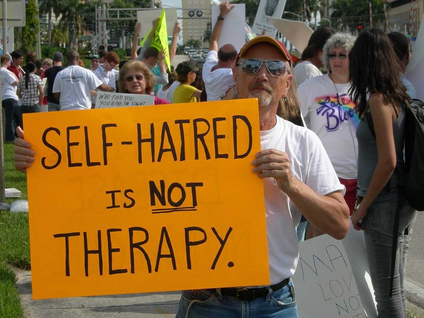 "Protester holds up sign: ""self hatred is not therapy."""